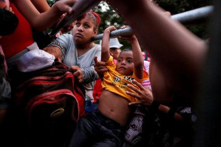 "People belonging to a caravan of migrants from El Salvador en route to the United States, board a pick-up truck for a hitchhike along the highway to Ciudad Tecun Uman, Guatemala from Moyuta, Guatemala, November 1, 2018. Jose Cabezas: ""I've seen a lot of children in the caravan, and in every boy and girl, I couldn't help but see the face of my own six-year-old son. I could feel the parents' fear, the frustration of not being able to give them a decent life. While trying to reach a caravan of Salvadoran migrants in the early hours of Nov. 1, we found a group of migrants sleeping on the side of the road. At dawn they started walking, hoping to get a lift. Eventually a small pickup stopped, and the driver said that he was only going to take mothers with children. At that moment I could see the uncertainty on the faces of the children who did not know what was happening. There were lots of dramas playing out. One woman was traveling to the United States with her two children of 11 and 1 1/2. She told me she only had $10 to reach the U.S. border, where she hoped to get a better job to provide for her children's future. There was talk about President Trump's threats to cut aid to El Salvador. Many said: ""Let him take it away, at the end of the day, none of us benefit from the aid anyway."" I've worked on migration since the start of my career. In El Salvador, it's been a constant theme in the country's history. Many people flee because of the social problems and political violence. But we haven't seen anything like this since the civil war in the 1980s."" REUTERS/Jose Cabezas/File photo"