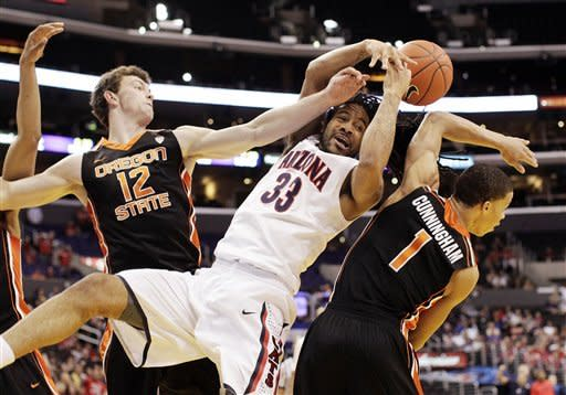 Arizona's Jesse Perry, center, fights for a rebound with Oregon State's Angus Brandt, left, and Jared Cunningham during the first half of an NCAA college basketball game in the semifinals of the Pac-12 conference championship in Los Angeles, Friday, March 9, 2012. (AP Photo/Jae C. Hong)