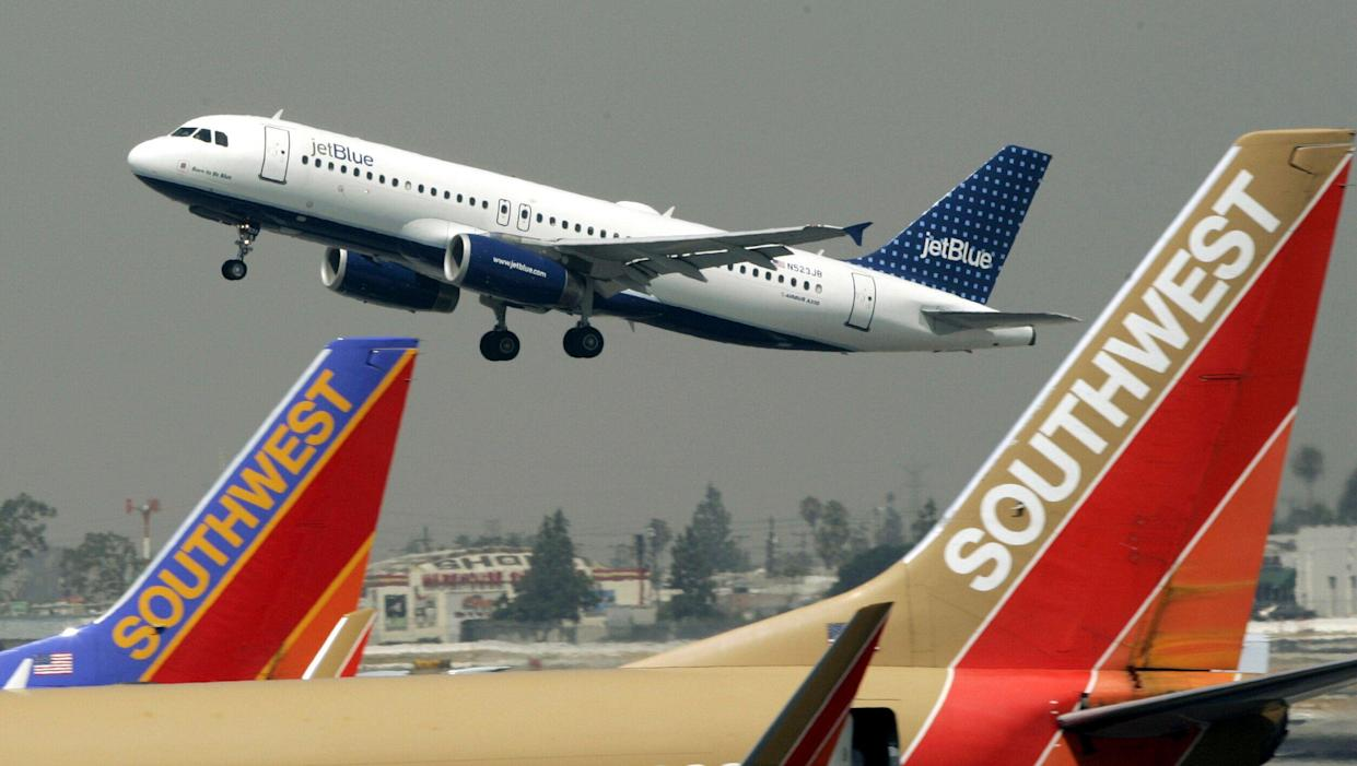 A JetBlue Airbus flies over a pair of Southwest Airlines' jets from Bob Hope Airport in Burbank, Calif., bound for New York's JFK airport. (Photo credit: AP/Reed Saxon, FILE)