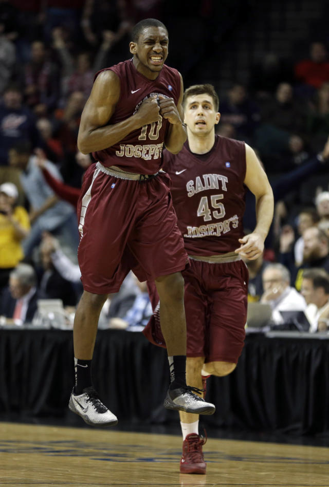 Saint Joseph's Langston Galloway, left, celebrates after a 3-point basket while Halil Kanacevic looks on during the second half of an NCAA college basketball game against VCU in the championship round of the Atlantic 10 Conference tournament at the Barclays Center in New York, Sunday, March 16, 2014. St. Joseph's defeated VCU 65-61. (AP Photo/Seth Wenig)