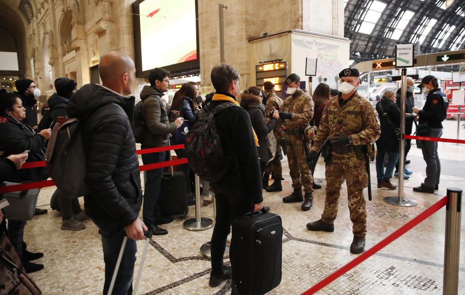 Two passengers with suitcases are stopped by armed guards with masks at a Milan train station.