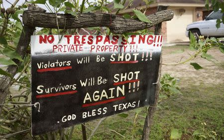 A handmade sign to deter trespassers hangs in the front yard of Fernando Rivera Jr.'s house in Brownsville, Texas September 2, 2014. REUTERS/Rick Wilking