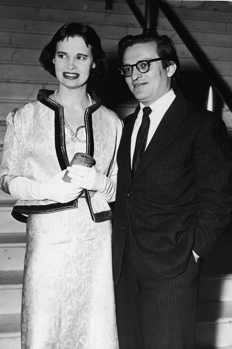 <p>Gloria and Lumet stand together at the foot of a marble staircase. </p>
