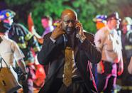 Philadelphia Mayor Michael Nutter speaks on a mobile phone as emergency responders search for passengers following an Amtrak train derailment in the Frankfort section of Philadelphia, Pennsylvania, May 12, 2015. An Amtrak passenger train with more than 200 passengers on board derailed in north Philadelphia on Tuesday night, killing at least five people and injuring more than 50 others, several of them critically, authorities said. Authorities said they had no idea what caused the train wreck, which left some demolished rail cars strewn upside down and on their sides in the city's Port Richmond neighborhood along the Delaware River. REUTERS/Bryan Woolston