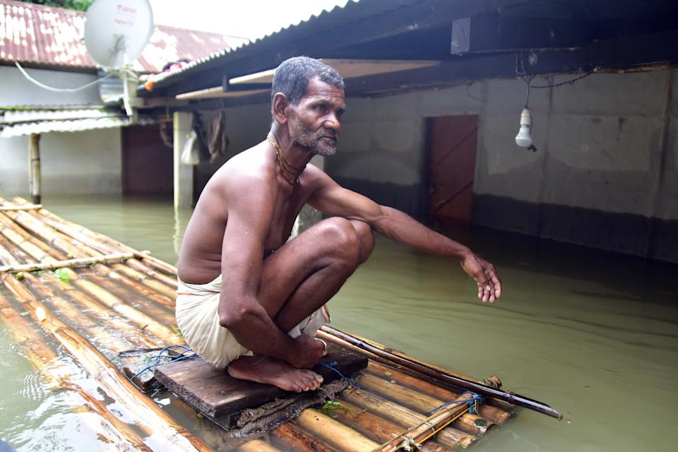 A man sits on a makeshift bamboo raft near his partially submerged house following flood due to monsoon rain at a village in Nagaon District of Assam. (Photo credit should read Anuwar Ali Hazarika/Barcroft Media via Getty Images)