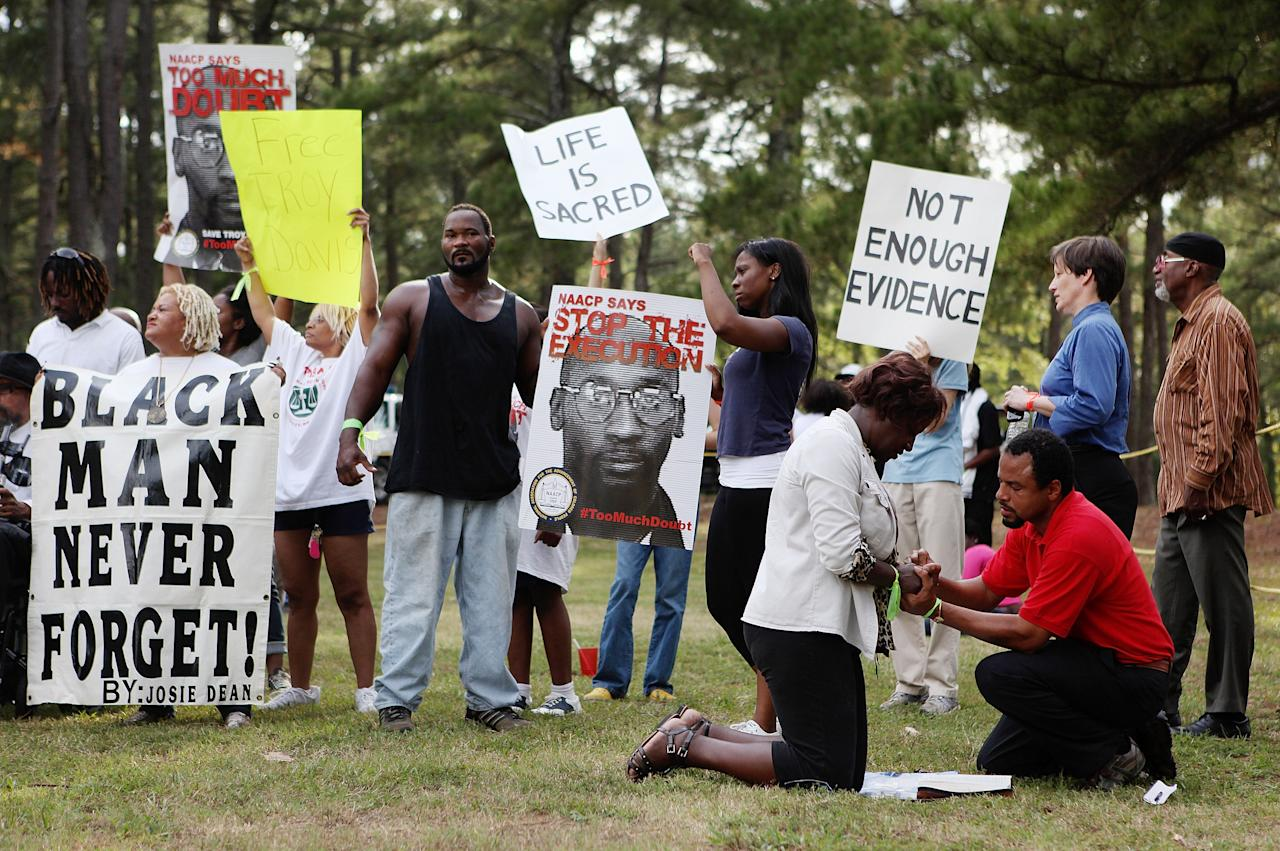 JACKSON, GA - SEPTEMBER 21:   Protestors pray together as they gather at Jackson State Prison for the planned execution of inmate Troy Davis on September 21, 2011 in Jackson, Georgia.  The Georgia Board of Pardons and Paroles denied clemency for death row inmate Troy Davis on Tuesday morning.  Davis is scheduled for execution at 7pm on Wednesday, September 21, 2011 for the 1989 slaying of off-duty Savannah, Ga., police officer Mark MacPhail. Controversy over Davis' guilt has drawn national attention to the case.  (Photo by Jessica McGowan/Getty Images)