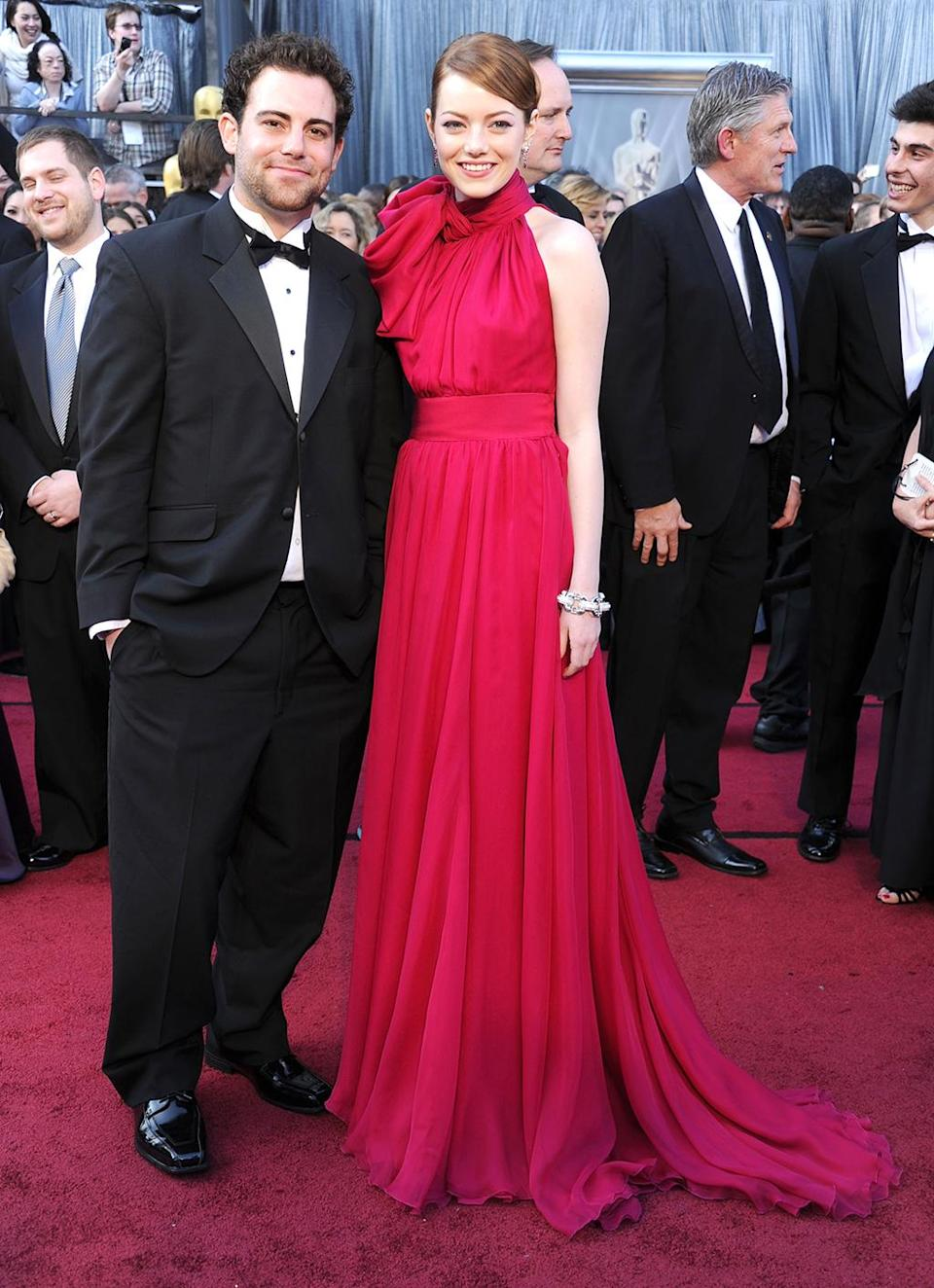 <p>Stone brought her brother, Spencer, to the 84th Annual Academy Awards, Feb. 26, 2012, to cheer on <em>The Help<em> — which was nominated for Best Picture. (Photo: Gregg DeGuire/FilmMagic) </em></em></p>