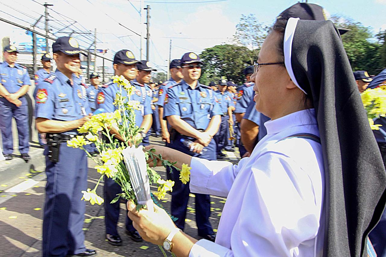 A Catholic nun gives flowers to police officers during the 27th anniversary of EDSA 1 People Power Revolution in Quezon City, north of Manila on 25 February 2013. EDSA People Power Revolution also known as the EDSA Revolution, or People Power) was a four-day series of non-violent mass demonstrations that toppled the Marcos dictatorship and installed Corazon Aquino as president in 1986. (Czeasar Dancel/NPPA Images)