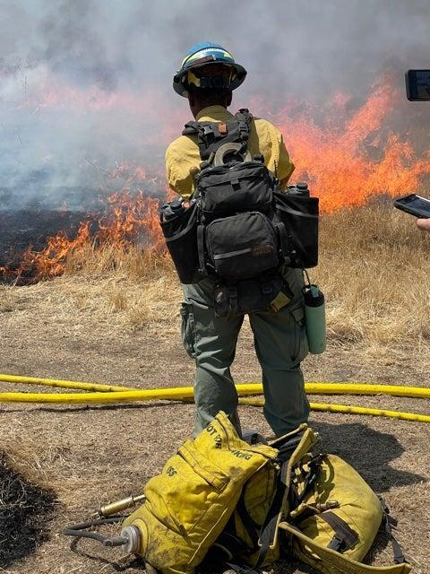 Inland Crew 5 firefighter Miracle Darnell monitors the fire line during a controlled burn (Louise Boyle/The Independent)
