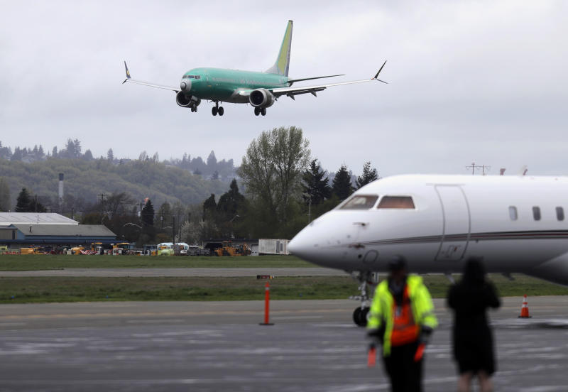 FILE - In this April 10, 2019, file photo a Boeing 737 MAX 8 airplane being built for India-based Jet Airways, top, lands following a test flight at Boeing Field in Seattle. Federal safety officials say Boeing should consider how cockpit confusion can slow the response of pilots who are dealing with the kind of problem that likely caused two airliners to crash in the past year. (AP Photo/Ted S. Warren, File)