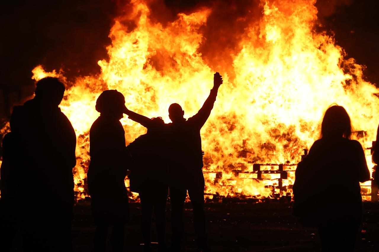 <p>People attend an 11th night Bonfire in the Sandy Row area of Belfast. (PA) </p>