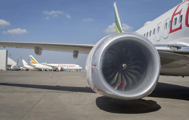 Other Ethiopian Airlines aircraft are seen in the distance behind an Ethiopian Airlines Boeing 737 Max 8 as it sits grounded at Bole International Airport in Addis Ababa, Ethiopia Saturday, March 23, 2019. The chief of Ethiopian Airlines says the warning and training requirements set for the now-grounded 737 Max aircraft may not have been enough following the Ethiopian Airlines plane crash that killed 157 people. (AP Photo/Mulugeta Ayene)