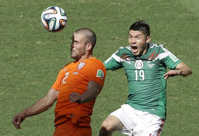 Netherlands' Ron Vlaar, left, and Mexico's Oribe Peralta go for a header during the World Cup round of 16 soccer match between the Netherlands and Mexico at the Arena Castelao in Fortaleza, Brazil, Sunday, June 29, 2014. (AP Photo/Themba Hadebe)