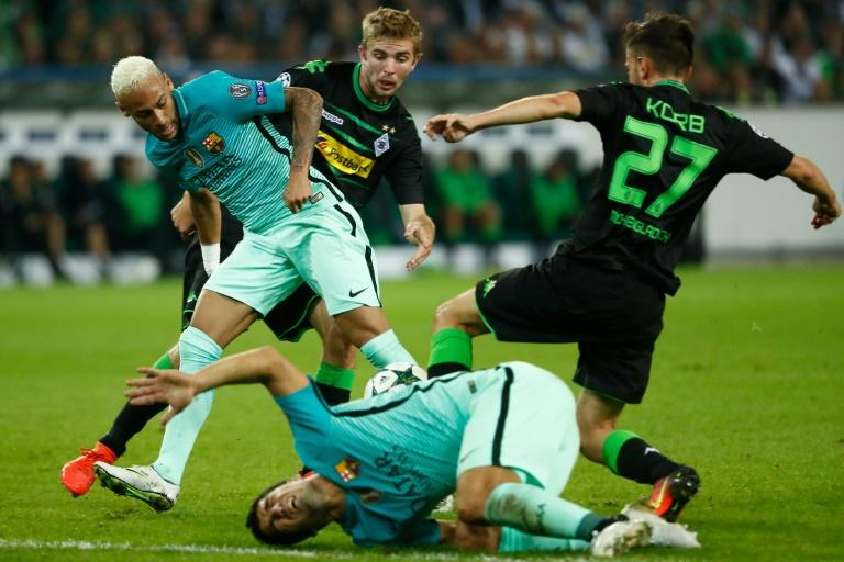Barcelona's Neymar (L) vies for the ball with Moenchengladbach's Christoph Kramer and Julian Korb (R) during the UEFA Champions League first-leg group C match