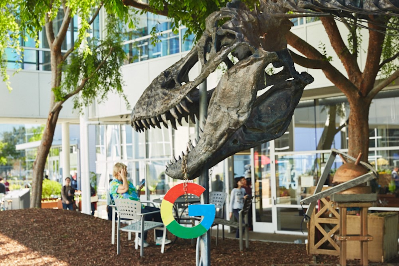 "A dinosaur head with the multicolor Google ""G"" hanging from its open mouth and a man sitting on a chair in front of a glass-walled building on the Googleplex campus."