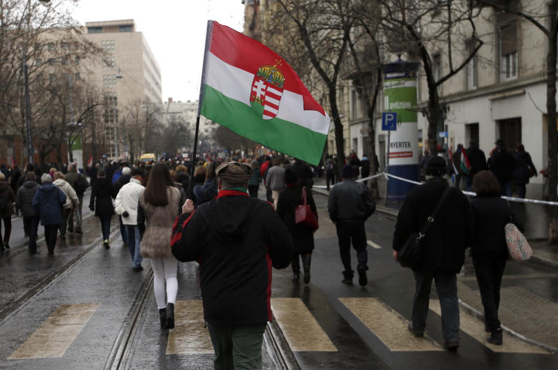 In this photo taken Thursday, March 15, 2018, a supporter of Hungarian Prime Minister Viktor Orban holds Hungary's national flag outside the Hungarian Parliament building in Budapest, Hungary. For decades after World War II, racist, extremist and anti-Semitic views were considered taboo in public life, strictly confined to the far-right fringes. Today they are openly expressed by mainstream political leaders in parts of Central and Eastern Europe, part of a global populist surge in the face of globalization and mass migration. (AP Photo/Darko Vojinovic)