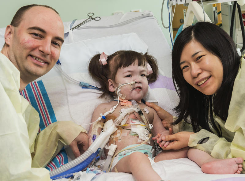 FILE - In this April 26, 2013 file photo provided by OSF Saint Francis Medical Center in Peoria, Ill., Darryl Warren and Lee Young-mi visit with their 2-year-old daughter Hannah Warren in a post-op room at Children's Hospital of Illinois in Peoria after having received a new windpipe in a landmark transplant operation April 9, 2013. Hannah, who was born in South Korea without a windpipe received a new one made from her own stem cells, died Saturday, July 6, 2013. She was the youngest patient in the world to benefit from the experimental treatment. (AP Photo/OSF Saint Francis Medical Center, Jim Carlson, File)