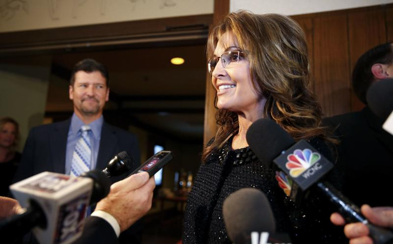 Former Republican governor of Alaska Sarah Palin speaks to members of the media as her husband Todd looks on before a celebration for evangelist Billy Graham's 95th birthday in Asheville, North Carolina November 7, 2013. REUTERS/Chris Keane (UNITED STATES - Tags: POLITICS RELIGION ENTERTAINMENT)