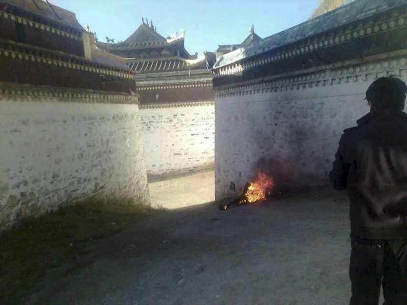 FILE - In this Oct. 22, 2012 file photo released by Freetibet.org, the burnt body of a Tibetan man identified as Dhondup is seen near a prayer hall at the remote Labrang Monastery in China's northwestern Gansu province. The Tibetan man in his 50s is believed to have died after setting himself on fire Monday in the latest protest against Chinese rule over the Himalayan region, the London-based rights group said. Chinese authorities are responding to an intensified wave of Tibetan self-immolation protests against Chinese rule by clamping down even harder — criminalizing the suicides, arresting protesters' friends and even confiscating thousands of satellite TV dishes. (AP Photo/Freetibet.org, File)