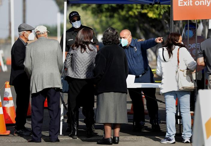 LOS ANGELES-CA-JANUARY 5, 2021: People line up at a checkpoint to be vaccinated at W. 79th Street and S. Mariposa Avenue in South Los Angeles on Tuesday, January 5, 2021. Los Angeles Fire Department officials turned people away who are not health care workers with the proper documentation and appointment. (Christina House / Los Angeles Times)