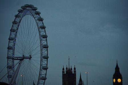FILE PHOTO: The London Eye is seen near the Houses of Parliament at dawn in central London October 21, 2013.  REUTERS/Toby Melville/File Photo