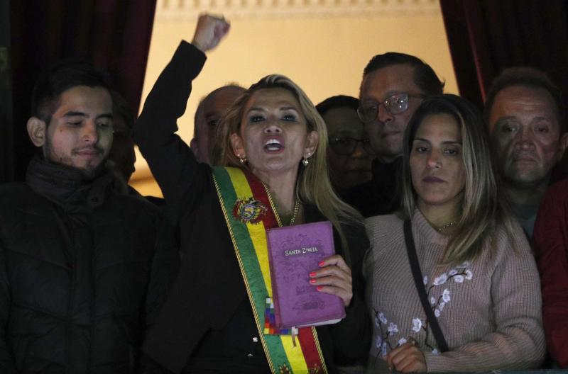 """In this Nov. 12, 2019, AP file photo, the Senate's second vice president and opposition politician Jeanine Añez, center, wearing the presidential sash and carrying a Bible, addresses the crowd from the balcony of the Quemado palace after she declared herself interim president of the country, in La Paz, Bolivia. """"The Bible has returned to the palace,"""" she told allies and the media that night in contrast to Evo Morales' presidency that celebrated the country's indigenous religious beliefs. (AP Photo/Juan Karita)"""