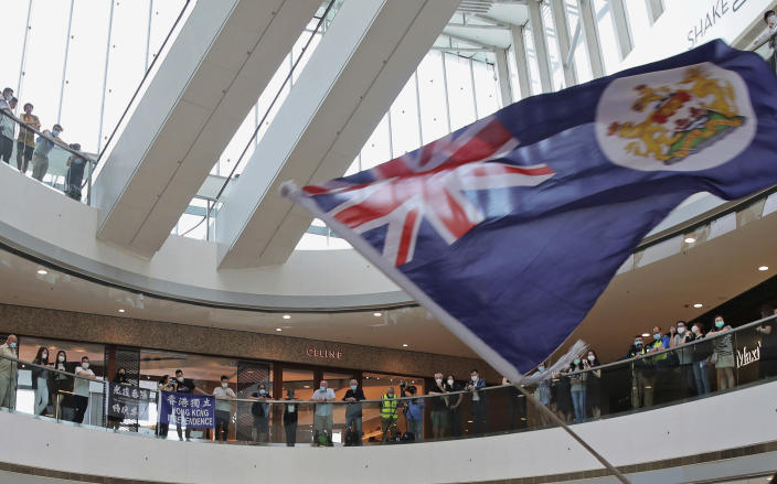 FILE - In this May 29, 2020, file photo, a protester holds a Hong Kong colonial flag in a shopping mall during a protest against China's national security legislation for the city, in Hong Kong. Thousands of people from Hong Kong are fleeing their hometown since Beijing imposed a draconian national security law on the territory in the summer 2020. Many say China's encroachment on their way of life and civil liberties has become unbearable, and they want to seek a better future for their children abroad. (AP Photo/Kin Cheung, File)