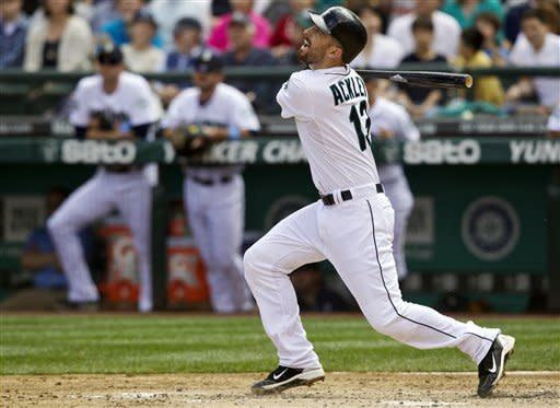 Seattle Mariners' Dustin Ackley hits a sacrifice fly to score Casper Wells against the San Francisco Giants in the second inning of a baseball game in Seattle, Sunday, June 17, 2012. (AP Photo/Stephen Brashear)