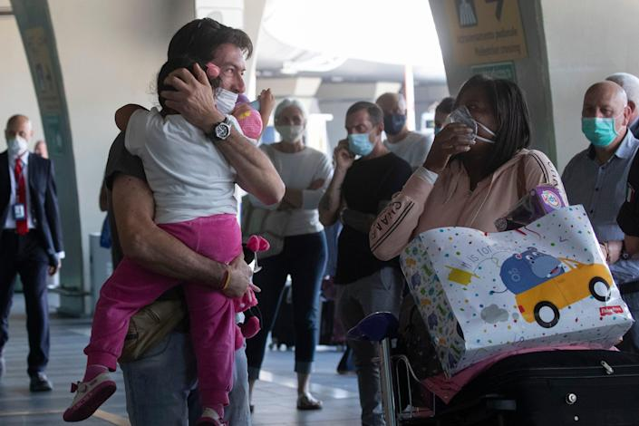 Sandro Manzato, from the Veneto region, hugs his daughter Yearline, 3, as she arrives with her mum Rubiela Perea, right, from Bogota, Colombia on June 3, 2020.