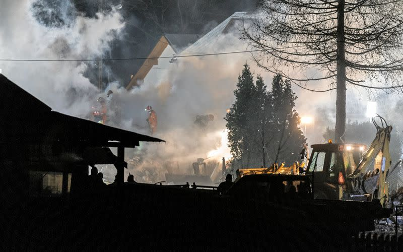 Firefighters work at the site of a building levelled by a gas explosion in Szczyrk,