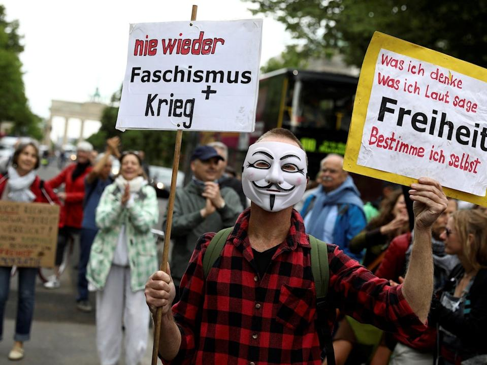 A demonstrator wearing a mask holds up signs during a protest against the government's restrictions, in Berlin on May 23, 2020.