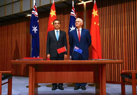 Australia's Prime Minister Malcolm Turnbull stands with Chinese Premier Li Keqiang before the start of an official signing ceremony at Parliament House in Canberra, Australia