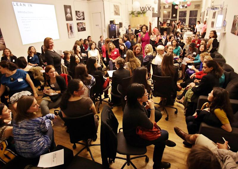"""This April 16, 2013 photo provided by Wix Lounge shows group facilitator Franne McNeal, right, standing, and organizer Mary Dove, standing left, addressing women at a """"Lean In"""" meeting in New York. The group is inspired by Facebook COO Sheryl Sandberg's book """"Lean In"""" which seeks to empower women in the workplace. (AP Photo/Wix Lounge, Galo Delgado)"""