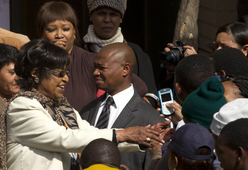 "Winnie Madikizela-Mandela, left, right, greets well wishers outside the Mediclinic Heart Hospital where former South African President Nelson Mandela is being treated in Pretoria, South Africa Thursday, July 18, 2013. Mandela will spend his 95th birthday in hospital on Thursday, but was said to be making ""remarkable"" progress. (AP Photo/Themba Hadebe)"