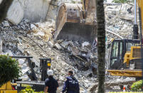 FILE - In this Thursday, July 8, 2021, file photo, excavators dig through the rubble of the Champlain Towers South, in Surfside, Fla. Officials announced a day earlier that they were switching their mission from rescue to recovery, but there is no plan to stop the private briefings for the families of those still missing. (Pedro Portal/Miami Herald via AP)