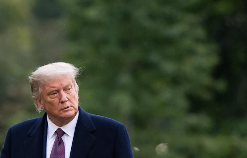 """US President Donald Trump walks from Marine One after arriving on the South Lawn of the White House in Washington, DC, October 1, 2020, following campaign events in New Jersey. - White House Chief of Staff Mark Meadows said on October 1, 2020, that he was optimistic about a rapid recovery for the president as he confirmed that Trump has """"mild symptoms"""" after testing positive for Covid-19. """"The president and the First Lady... remain in good spirits,"""" Meadows told reporters. (Photo by SAUL LOEB / AFP) (Photo by SAUL LOEB/AFP via Getty Images)"""