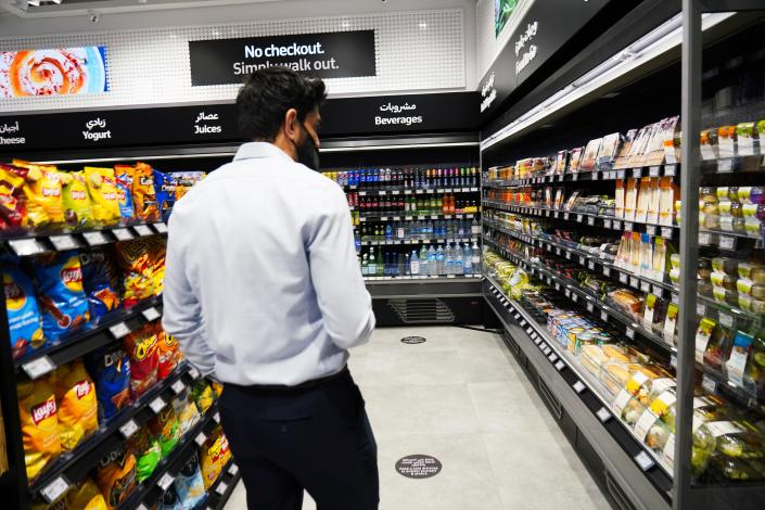 A Carrefour employee walks through Carrefour's new cashier-less grocery store in Mall of the Emirates in Dubai, United Arab Emirates, Monday, Sept. 6, 2021. The Middle East on Monday got its first completely automated cashier-less store, as retail giant Carrefour rolled out its vision for the future of the industry in a cavernous Dubai mall. (AP Photo/Isabel DeBre)