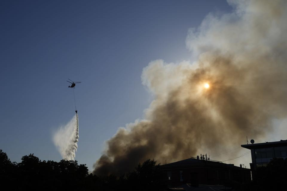 A Russian Emergency Situations Ministry helicopter dumps water on fire at a warehouse in Moscow, Russia, Saturday, June 19, 2021. A large fire broke out at a fireworks depot in the center of Moscow. The fire is raging at the area of 500 square meters, Russia emergency services said in the statement. (AP Photo/Pavel Golovkin)