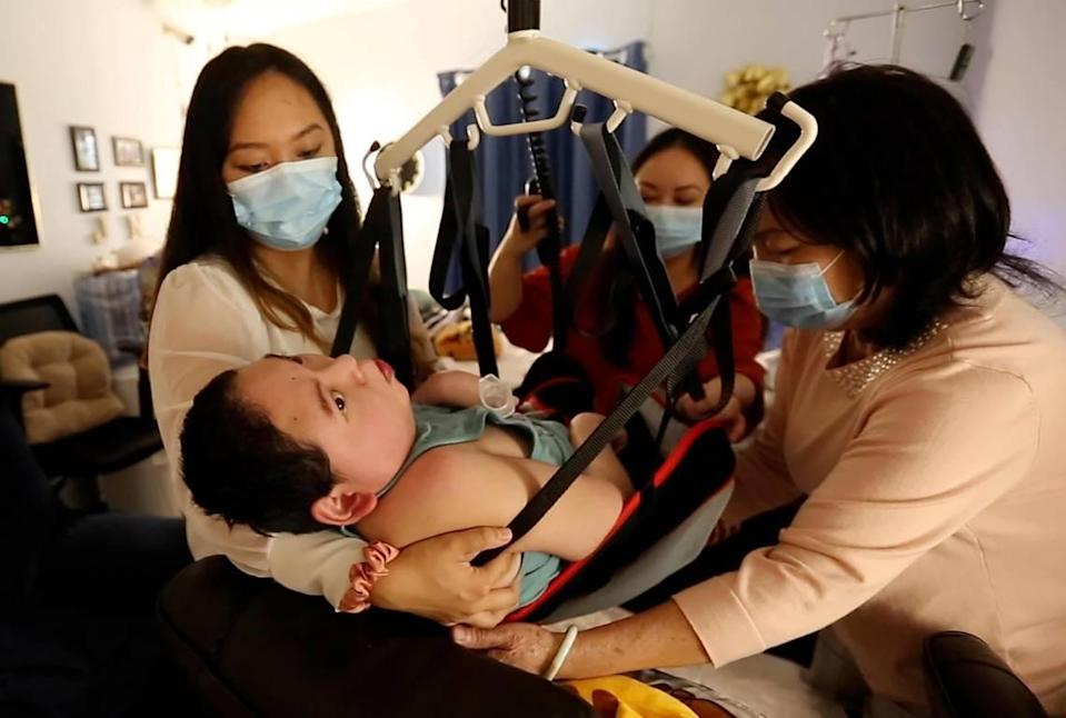 Justin Nguyen, 24, is supported by his sisters, Jennifer and Jessica Pham, and his mother, Julie Nguyen, as they use a Hoyer lift to help transfer him from his bed to a chair in his bedroom in their Jacksonville home. Justin suffered severe brain damage at birth.