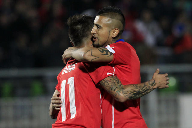 Chile's Arturo Vidal, right, celebrates with Eduardo Vargas after scoring against Northern Ireland during an international friendly soccer match, in Valparaiso, Chile, Wednesday, June 4, 2014. (AP Photo/Luis Hidalgo)