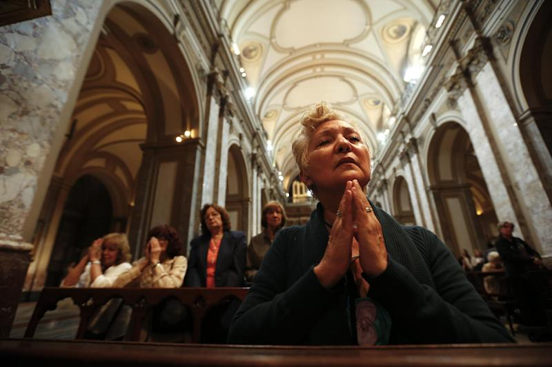 A woman prays inside the Metropolitan Cathedral in Buenos Aires, Argentina,  Wednesday, March 13, 2013.  White smoke billowed from the chimney of the Sistine Chapel, Wednesday evening, in Vatican City, meaning 115 cardinals in a papal conclave elected a new leader for the world's 1.2 billion Catholics. (AP Photo/Victor R. Caivano)