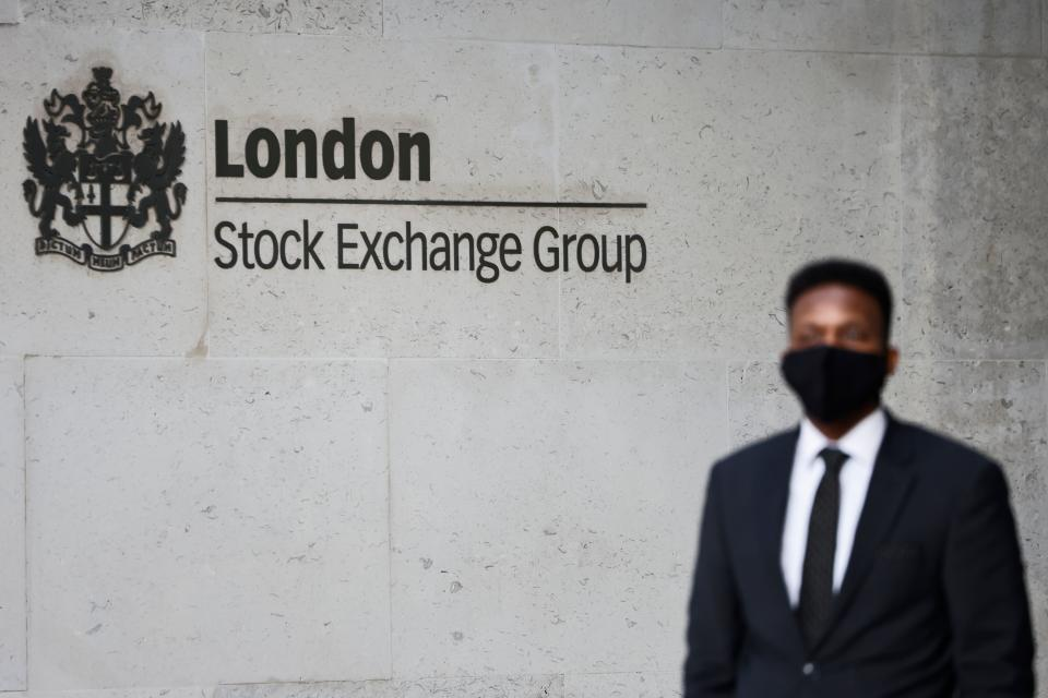 A security guard stands beside the logo for the London Stock Exchange Group outside the stock exchange in London on December 29, 2020. - The London stock market soared on December 29 as investors gave their initial verdict on Britain's Brexit deal with the EU, while eurozone equities also rose on upbeat US stimulus news, with Frankfurt extending its record breaking run. (Photo by Tolga Akmen / AFP) (Photo by TOLGA AKMEN/AFP via Getty Images)