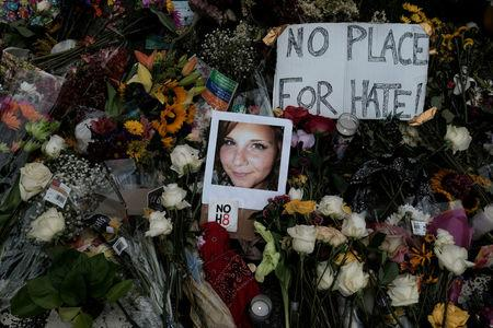 """FILE PHOTO: A photograph of Charlottesville victim Heather Heyer is seen amongst flowers left at the scene of the car attack on a group of counter-protesters that took her life during the """"Unite the Right"""" rally as people continue to react to the weekend violence in Charlottesville, Virginia, U.S. on August 14, 2017.  REUTERS/Justin Ide/File Photo"""