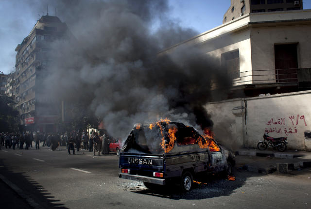"A police pickup truck burns after being set on fire by Egyptian Ultras, hard-core soccer fans, during an anti government rally in front of the Giza security directorate, background, in Giza, Egypt, Wednesday, March 6, 2013. Hundreds of Ultras rallied to the Giza security directorate chanting anti government slogans, launching fireworks toward the security facility and setting a police pickup truck on fire. Arabic on the wall at right, reads ""March 9th, retribution, hurt the interior ministry."" (AP Photo/Nasser Nasser)"