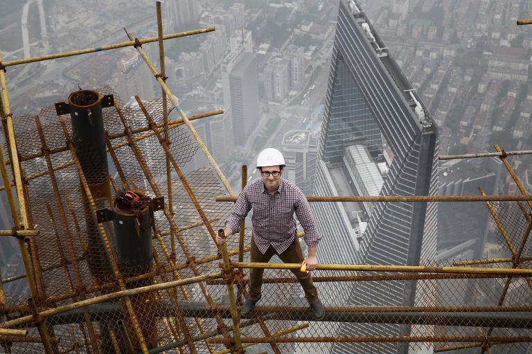 """Architect Danny Forster, the host of """"How China Works"""", a three-part series that will air on The Discovery Channel, stands on building scaffolding high above Shanghai"""