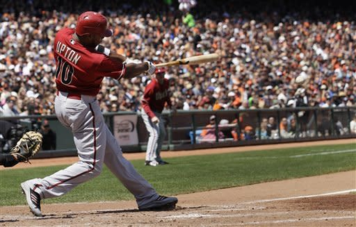 Arizona Diamondbacks' Justin Upton (10) doubles to score Trevor Cahill against the San Francisco Giants during the third inning of a baseball game in San Francisco, Monday, May 28, 2012. (AP Photo/Jeff Chiu)