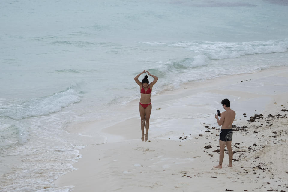Tourists spend time on the beach in Cancun, Mexico, Saturday, June 13, 2020. An irony of the coronavirus pandemic is that the idyllic beach vacation in Mexico in the brochures really does exist now: the white sand beaches are sparkling clean and empty on the Caribbean coast. (AP Photo/Victor Ruiz)