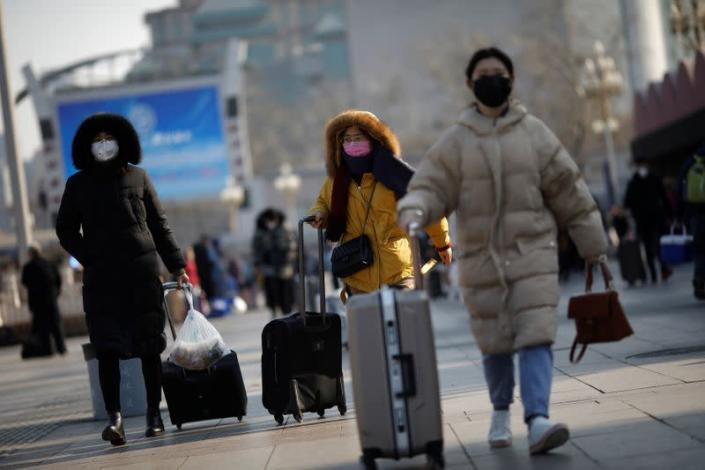 People wearing face masks walks outside Beijing Railway Station as the country is hit by an outbreak of the new coronavirus, in Beijing