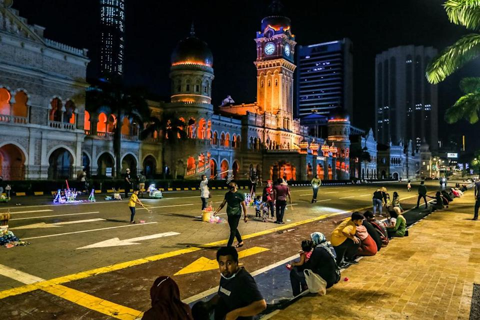 People wearing face masks are pictured at Dataran Merdeka during the conditional movement control order (CMCO) in Kuala Lumpur December 5, 2020. — Picture by Firdaus Latif