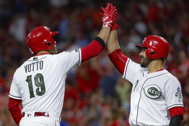 Cincinnati Reds' Joey Votto (19) celebrates with Eugenio Suarez (7) after hitting a solo home run off Chicago Cubs starting pitcher Yu Darvish in the sixth inning of a baseball game, Friday, Aug. 9, 2019, in Cincinnati. (AP Photo/John Minchillo)